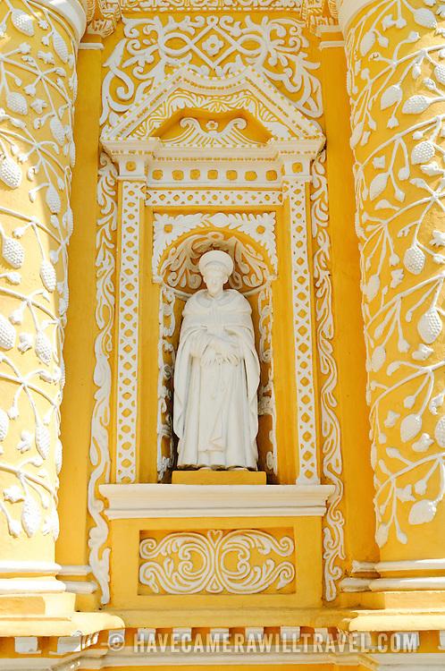 White statue that is part of the distinctive  and ornate yellow and white exterior of the Iglesia y Convento de Nuestra Senora de la Merced in downtown Antigua, Guatemala.