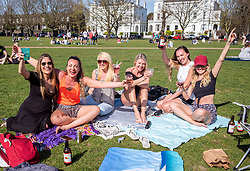 © Licensed to London News Pictures. 30/03/2021. London, UK. Friends celebrate the warm weather and more freedoms with a picnic on Richmond Green, South West London as weather forecasters predict the hottest March in over 50 years with highs of 23c in the South East today. From yesterday, two households or six people are now allowed to meet up marking the end of the Stay at Home advice. Playing golf, tennis and organised outdoor sports is also allowed as England starts to unlock after a year of Covid-19 restrictions. Photo credit: Alex Lentati/LNP