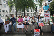 A line of supporters rest in the shade in Parliament Square after a hot march from the Israeli Embassy.<br /> <br /> Tens of thousands of protesters marched in Central London to show their outrage against the Israeli onslaught on Gaza.
