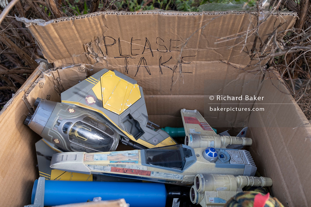 The discarded possessions of a young boy, part of a winter's decluttering, consists of Star War model toys including a Light Sabre and Star Fighter, in a box for passers-by to take for free from a wall outside a residential home in Herne Hill, south London, on 28th January 2021, in London, England.