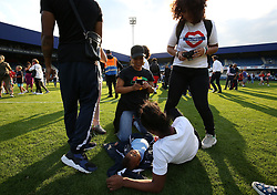 2 September 2017 - Charity Football - Game 4 Grenfell - Grenfell friends and family take photos of a baby on the pitch - Photo: Charlotte Wilson