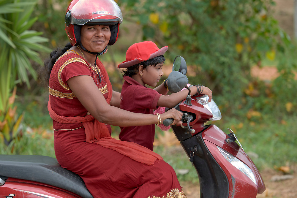 A woman and her child on a motorbike in Parantan, Kilinochchi, Sri Lanka. The woman participates in a church-sponsored women's group, many of whose members are widows whose husbands were killed during the country's brutal civil war.