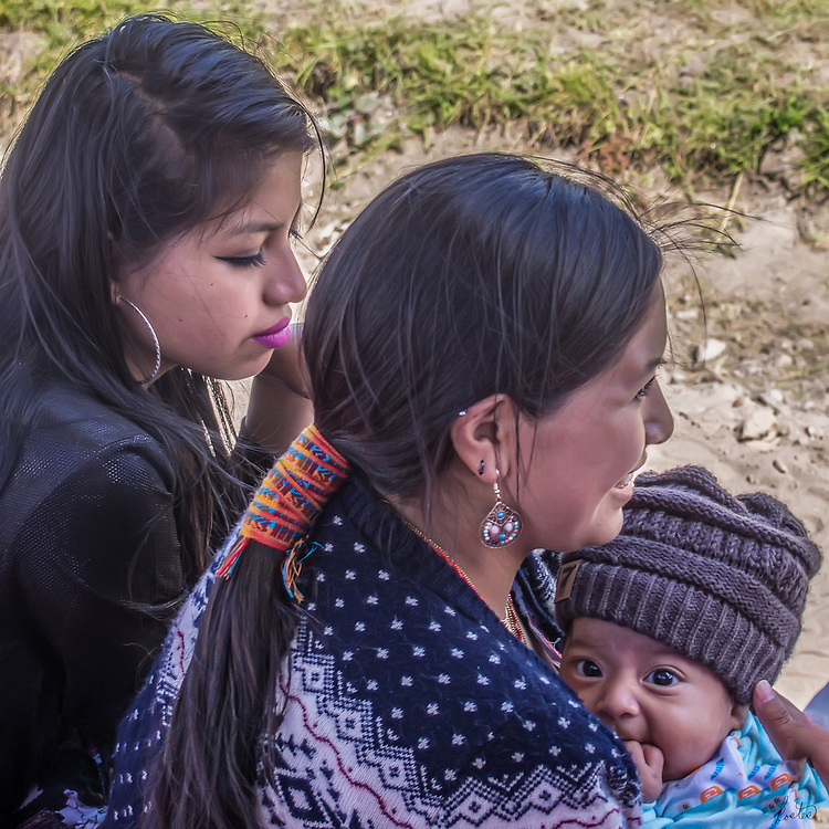 A Kichwa woman with her child and a friend at a Kapak Raymi ceremony in Cotacachi, Ecuador