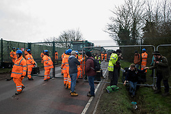 Harefield, UK. 8 February, 2020. Activists climb through a ditch after HS2 engineers tried to prevent environmental activists from Save the Colne Valley, Stop HS2 and Extinction Rebellion from accessing an area of Harvil Road fenced off in order to carry out tree felling works for the high-speed rail project. The activists were successful in preventing any of the scheduled tree felling by HS2 and after an intervention by a police officer all tree felling and strimming work has now been cancelled for the weekend.