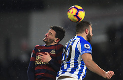 Newcastle United's Fabian Schar (left) and Huddersfield Town's Laurent Depoitre (right) battle for the ball during the Premier League match at the John Smith's Stadium, Huddersfield.