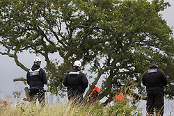 Steeple Claydon, 23rd September, 2020. National Eviction Team enforcement agents watch tree surgeons working on behalf of HS2 Ltd fell a 200-year-old oak tree alongside the East West Rail route known locally as the '7 Sisters Oak' as part of works connected to the HS2 high-speed rail link. A small group of local people and anti-HS2 activists based at the nearby Poors Piece Conservation Project also observed the felling of the tree, which was home to bats and other species, whilst monitored by a joint force of around fifty bailiffs, security guards and police officers from Thames Valley Police.