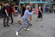 Man dancing on Oxford Street in London, England, United Kingdom. Listening to music on his headphones this dancer joined in with another practicing his street dance moves on this busy shopping street.