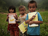 Three kids come back from school. They hold their notebook and pen. Their clothes are dirty.  Ha Giang province, Vietnam, Asia