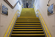 As the second week of the Coronavirus lockdown continues the UK death toll rises by 569 to 2,921, with 1m figure reported cases of Covid-19 being passed worldwide, a solitary train passenger is about to descend  yellow steps leading up to a platform of Herne Hill rail station in south London, on 2nd April 2020, in London, England.