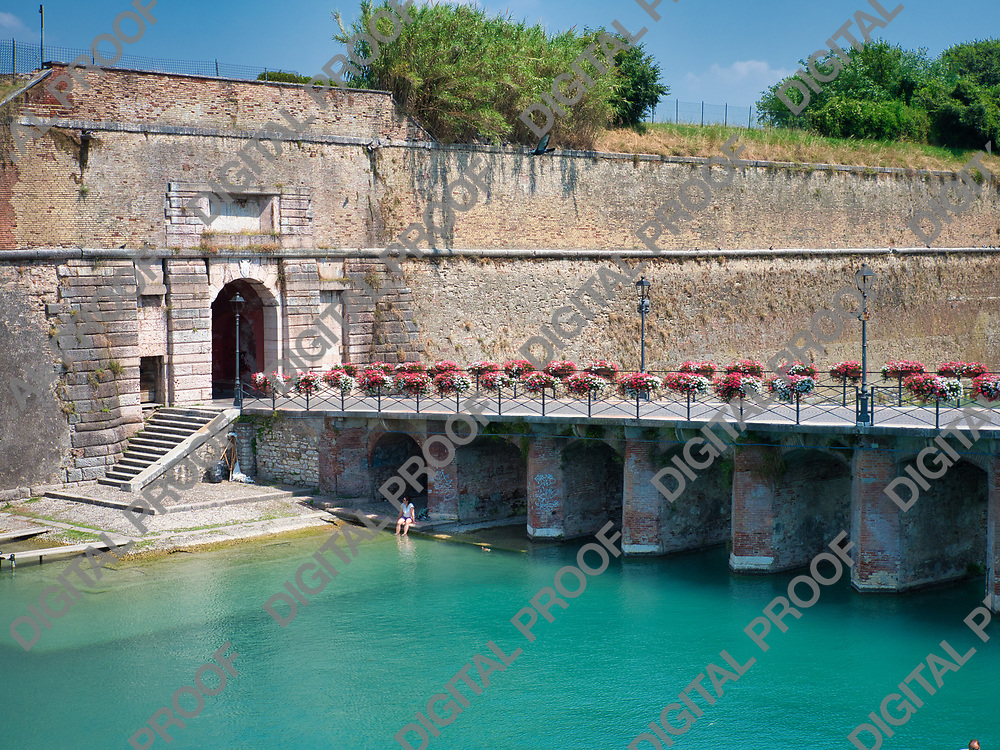 An unrecognizable person rests under the bridge at the entrance to the village of Peschiera del Garda on Lake Garda, Italy during a summer afternoon