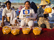 "02 JANUARY 2015 - KHLONG LUANG, PATHUM THANI, THAILAND: People pray and wait for monks to coma past them at Wat Phra Dhammakaya at the start of the 4th annual Dhammachai Dhutanaga (a dhutanga is a ""wandering"" and translated as pilgrimage). More than 1,100 monks are participating in a 450 kilometer (280 miles) long pilgrimage, which is going through six provinces in central Thailand. The purpose of the pilgrimage is to pay homage to the Buddha, preserve Buddhist culture, welcome the new year, and ""develop virtuous Buddhist youth leaders."" Wat Phra Dhammakaya is the largest Buddhist temple in Thailand and the center of the Dhammakaya movement, a Buddhist sect founded in the 1970s.   PHOTO BY JACK KURTZ"