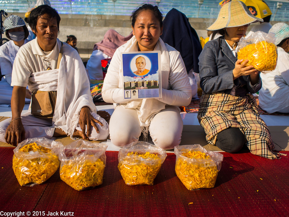"""02 JANUARY 2015 - KHLONG LUANG, PATHUM THANI, THAILAND: People pray and wait for monks to coma past them at Wat Phra Dhammakaya at the start of the 4th annual Dhammachai Dhutanaga (a dhutanga is a """"wandering"""" and translated as pilgrimage). More than 1,100 monks are participating in a 450 kilometer (280 miles) long pilgrimage, which is going through six provinces in central Thailand. The purpose of the pilgrimage is to pay homage to the Buddha, preserve Buddhist culture, welcome the new year, and """"develop virtuous Buddhist youth leaders."""" Wat Phra Dhammakaya is the largest Buddhist temple in Thailand and the center of the Dhammakaya movement, a Buddhist sect founded in the 1970s.   PHOTO BY JACK KURTZ"""