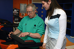 Instructor showing young woman how to use the treadmill at an inclusive fitness gym,