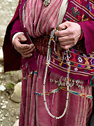 A Brokpa woman wearing her traditional clothing holds Buddhist rosary beads in Merak, Eastern Bhutan.  The Brokpa, the semi-nomads of the villages of Merak and Sakteng are said to have migrated to Bhutan a few centuries ago from the Tshona region of Southern Tibet. Thriving on rearing yaks and sheep, the Brokpas have maintained many of their unique traditions and customs.