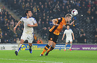 Hull City's Michael Dawson heads clear under pressure from Leicester City's Shinji Okazaki<br /> <br /> Photographer Chris Vaughan/CameraSport<br /> <br /> Football - Capital One Cup Round 4 - Hull City v Leicester City - Tuesday 27th October 2015 - Kingston Communications Stadium - Hull<br />  <br /> © CameraSport - 43 Linden Ave. Countesthorpe. Leicester. England. LE8 5PG - Tel: +44 (0) 116 277 4147 - admin@camerasport.com - www.camerasport.com