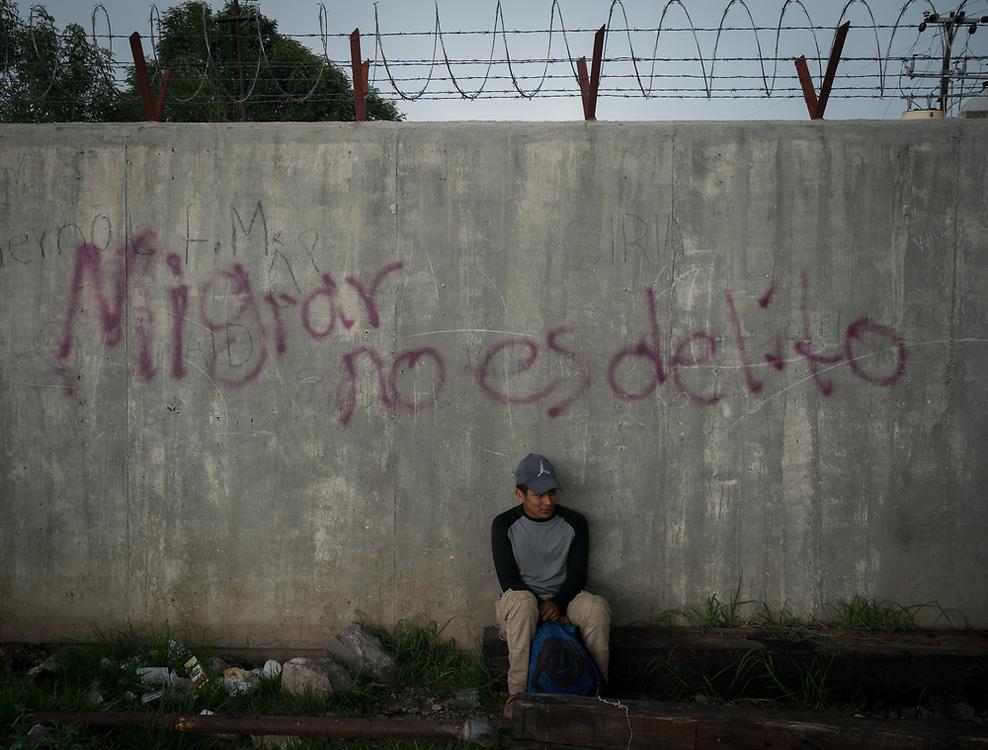 A Honduran migrant, waits for the train known as La Bestia in Apizaco, Mexico. Behind him, graffiti on the wall says 'Migrar no es delito'... migrating isn't a crime.