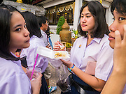 """27 NOVEMBER 2012 - BANGKOK, THAILAND:  School girls share a snack on the midway at the Wat Saket Temple Fair in Bangkok. Thailand is facing a rising tide of gun violence and is wrestling with how to curb it. Despite strict gun control laws, more and more guns are showing up in the country. Wat Saket, popularly known as the Golden Mount or """"Phu Khao Thong,"""" is one of the most popular and oldest Buddhist temples in Bangkok. It dates to the Ayutthaya period (roughly 1350-1767 AD) and was renovated extensively when the Siamese fled Ayutthaya and established their new capitol in Bangkok. The temple holds an annual fair in November, the week of the full moon. It's one of the most popular temple fairs in Bangkok. The fair draws people from across Bangkok and spills out in the streets around the temple.   PHOTO BY JACK KURTZ"""
