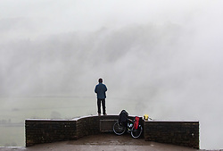 © Licensed to London News Pictures. 07/12/2020. Surrey, UK. A cyclist stops to enjoy the misty views from the top of Box Hill, Surrey as the Met Office issue a yellow weather warning for freezing fog with disruption to transport for the South East of England today with temperatures near 0c. The Government is expected to rolling out the new Pfizer/BioNTech's coronavirus vaccine tomorrow with reports it has already arrived in the UK for distribution to hospitals around the country. Photo credit: Alex Lentati/LNP