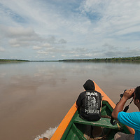 Peruvian Indian guides scan the Amazon River for freshwater dolphins.