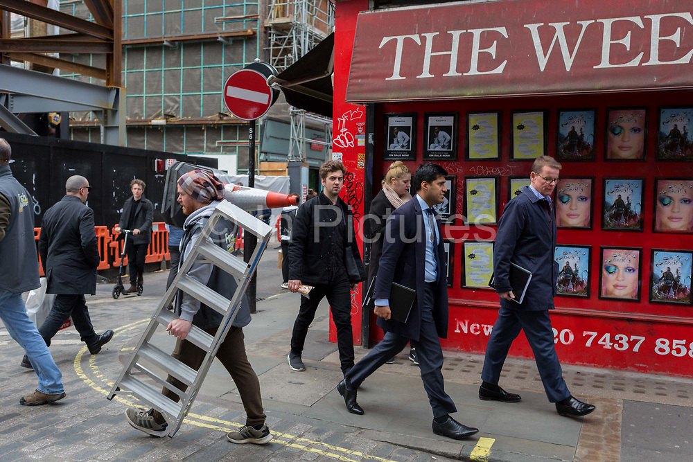 A workman carries a traffic cone through streets of the West End. on 7th March 2019, in London, England.