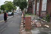 Street scene of a Muslim woman passing a derelict building in Moseley, Birmingham, United Kingdom. Moseley is known as one of the more up market neighbourhoods in Birmingham, but still shows signs of downturn, and lack of consistent investment and general upkeep away from the residential areas, like here on Moseley Road.