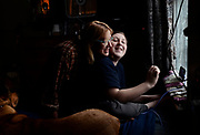 Rebecca Ribeiro, left, hugs her son, Max Ribeiro, 12, right, as he plays an online video game on his mother's phone, while his mother,  at their home in Newfield, NY, Saturday, January 6, 2018. At left is one of the family's dogs, Sawyer. The Ribiero's don't own a computer, and only use their phones for internet access.  The Ribeiro's bedroom is the best place to pick up the internet remotely. Max, who has a language processing disorder, receives special care at school funded by his CHIP coverage. The Ribeiro's worry about what will happen if CHIP ends. <br /> (Heather Ainsworth for The New York Times)