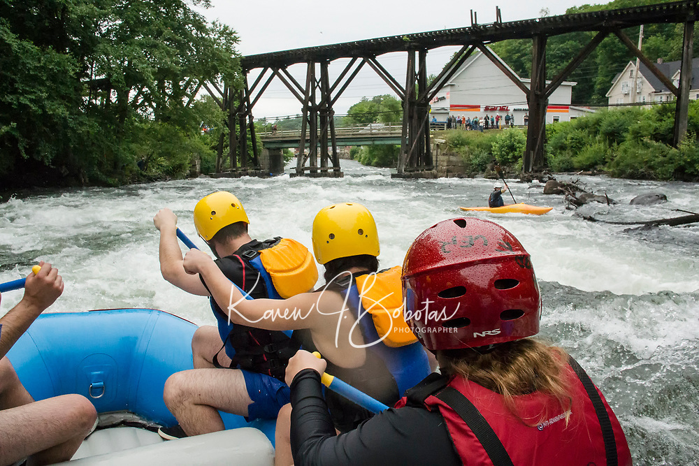 """Joe Astle, Jenisha Shrestha and Alicia Carroll paddle hard as they approach the trestle during Franklin's first whitewater festival """"Winni River Days"""" with Mill City Park Saturday afternoon.  (Karen Bobotas/for the Laconia Daily Sun)"""