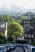 Terraced homes and parked cars with an elevated viewpoint of the London skyline at Crystal Palace, on 16th June 2021, in London, England.