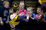 Natalie Wojcik of the Michigan Wolverines high fives young fans in between events at the Elevate the Stage meet at the Huntington Center on February 23, 2019 in Toledo, Ohio.