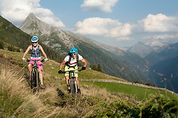Two mountain bikers riding on uphill in alpine landscape, Zillertal, Tyrol, Austria