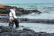 30 JULY 2013 - KOH SAMET, RAYONG, THAILAND:  An oil spill cleanup worker stands in the surf on Ao Prao beach on Koh Samet island. About 50,000 liters of crude oil poured out of a pipeline in the Gulf of Thailand over the weekend authorities said. The oil made landfall on the white sand beaches of Ao Prao, on Koh Samet, a popular tourists destination in Rayong province about 2.5 hours southeast of Bangkok. Workers from PTT Global, owner of the pipeline, and up to 500 Thai military personnel are cleaning up the beaches. Tourists staying near the spill, which fouled Ao Prao beach, were evacuated to hotels on the east side of the island, which was not impacted by the spill. PTT Global Chemical Pcl is part of state-controlled PTT Pcl, Thailand's biggest energy firm.     PHOTO BY JACK KURTZ