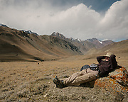 "Paul Salopek taking a break. Place called Loop Suk, meaning ""Large Point"" in Wakhi. Trekking up the Tash Köpruk valley, leading to the Irshad Pass (4950m) into Pakistan. Guiding and photographing Paul Salopek while trekking with 2 donkeys across the ""Roof of the World"", through the Afghan Pamir and Hindukush mountains, into Pakistan and the Karakoram mountains of the Greater Western Himalaya."