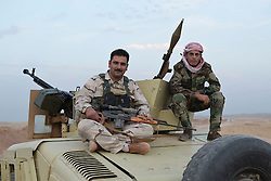 © Licensed to London News Pictures. 30/09/2015. Kirkuk, Iraq. Two Kurdish peshmerga fighters wait on the back of an armoured Humvee for the start of an offensive to re-take 11 villages from ISIS in the Kirkuk, Iraq, area.<br /> <br /> Supported by large amounts of coalition airstrikes, members of the Iraqi-Kurdish peshmerga today (30/09/2015) took part in an offensive to take seven villages across a large front near Kirkuk, Iraq. By mid afternoon the Kurds had reached most of their objectives, but suffered around 10 casualties all to improvised explosive devices. All seven villages were originally Kurdish and settled with other ethnic groups during the Iraqi Arabisation process of the 1970's and 80's. Photo credit: Matt Cetti-Roberts/LNP
