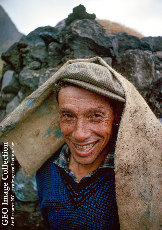 An islander at a thatching bee wears a bit of burlap in fun.