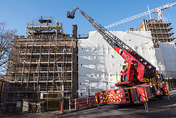 © Licensed to London News Pictures. 07/01/2018. Bristol, UK.  Fire Service personnel damp down damage to the roof of the Fry Building at the University of Bristol, following a fire on the evening of 06/01/2018. The building has been undergoing refurbishment and was due to open for students in September this year. The fire started on the top floor of the five-storey building, and Avon Fire and Rescue sent multiple fire appliances to the scene including two turntable ladders. No one was in the building when the fire started and there were no injuries.  Photo credit: Simon Chapman/LNP