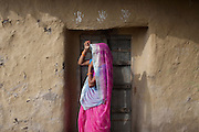 Malti Devi, 40, a housewife and the mother of Kanchan Kumari Sharma, 12, (name changed)  is covering her head with a pink sari while standing in front of their home in Sersiya Kekrahi village, Varanasi District, Uttar Pradesh, India. In 2012, Kanchan went with a friend to bring lunch to her father, around 2 km away from her home. On the way they met Rajesh (rapist) and Ashok, a friend of his. Both girls were picked up on the spot using an excuse. Ashok drove Kanchan's friend home, but Rajesh forced Kanchan to travel with him during six days and for hundreds of kilometres across different states. (Mirzapur / Chennai / Itarsi / Bhusawal) He raped her once behind the station in Itarsi. With great effort and some coincidence, the uncle of Kanchan managed to bring her back home. Although she was scared, she insisted on going to the police to file a case (FIR). She was kept at the police station for 12 days and threatened to prevent her from filing an official case. Ashok and Rajesh are from higher caste and wealthy families. While Rajesh spent 24 days in jail initially in summer 2012, he is now a free man while the trial is still going on. Kanchan's family is now struggling to put together 30.000 Indian Rupees (500 USD) to continue battling for justice in court.
