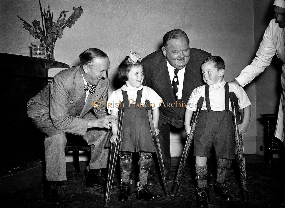 """Laurel and Hardy present cheque on behalf of Premier (DOMAS) to Little Willie Fund.22/09/1953..Laurel and Hardy were one of the most popular and critically acclaimed comedy double acts of the early Classical Hollywood era of American cinema. Composed of thin Englishman Stan Laurel (1890-1965) and heavy American Oliver Hardy (1892-1957) they became well known during the late 1920s to the mid-1940s for their slapstick comedy, with Laurel playing the clumsy and childlike friend of the pompous Hardy.[1] They made over 100 films together, initially two-reelers (short films) before expanding into feature length films in the 1930s. Their films include Sons of the Desert (1933), the Academy Award winning short film The Music Box (1932), Babes in Toyland (1934), and Way Out West (1937). Hardy's catchphrase """"Well, here's another nice mess you've gotten me into!"""" is still widely recognized."""