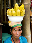 A woman selling corn from a bowl resting on her head, Bedugal market, Bali, Indonesia