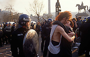 A couple kiss near police officers in the middle of the Poll Tax riot in the UK capital, on 31st March 1990, in Trafalgar Square, London, England. Angry crowds, demonstrating against Margaret Thatchers local authority tax, stormed the Whitehall area and then Londons West End, setting fire to a construction site and cars, looting stores up Charing Cross Road and St Martins Lane. The anti-poll tax rally in central London erupted into the worst riots seen in the city for a century. Forty-five police officers were among the 113 people injured as well as 20 police horses. 340 people were arrested.