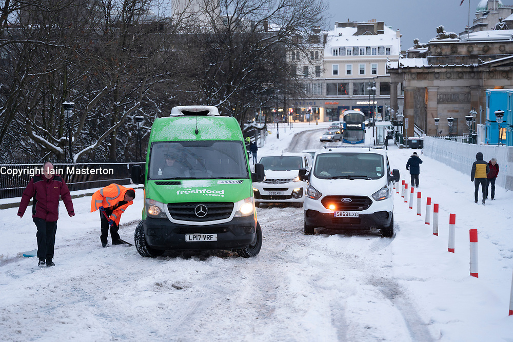 Edinburgh, Scotland, UK. 10 Feb 2021. Big freeze continues in the UK with heavy overnight and morning snow bringing traffic to a standstill on many roads in the city centre. Pic; People free cars stuck on The Mound.  Iain Masterton/Alamy Live news
