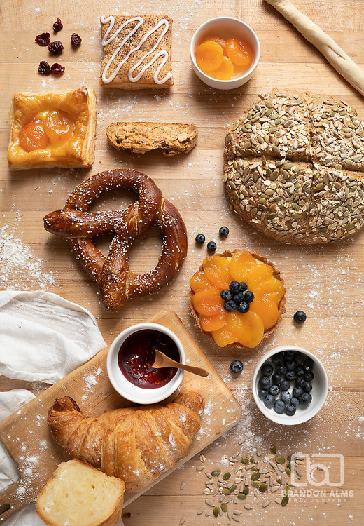 An assortment of baked goods made by Katie Kring; owner of the B+B Boulangerie. From top to bottom and left to right; the baked goods pictured here are as follows: Chocolate Toaster Strudel; Sunny Sideup Apricot Danish; Almond Biscotti; Scandinavian seed bread;Bavarian Pretzel; Apricot Blueberry Tart; and Classic Croissants. By Brandon Alms Photography