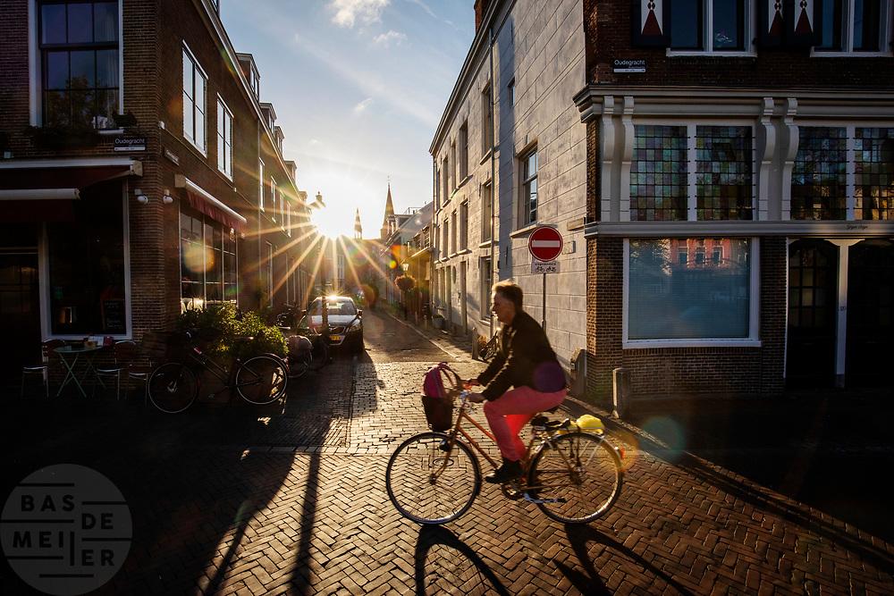Een man fietst in het avondlicht door Utrecht.<br /> <br /> A man cycles in the evening in Utrecht.