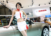 A model poses for photographs on a car during Shanghai Motor Show, in Shanghai, China, on April 20, 2009. Shanghai auto show opened Monday for the press and will be open April 24-28 for the public. China is the only major auto market still growing despite the global economic slowdown. U.S. and global auto makers see China as the place where they can find the sales they desperately lack in their home market. Chinese automakers see the opportunity to assess themselves as major players in the world market. Photo by Lucas Schifres/Pictobank