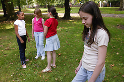 Three girls excluding their friend from their conversation,
