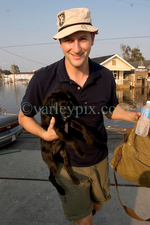05 Sept  2005. New Orleans, Louisiana. Post hurricane Katrina.<br /> Animal rescue boat. Daily Mirror's Ryan Parry rescues a puppy from the devastating floods in Uptown New Orleans.<br /> Photo; ©Charlie Varley/varleypix.com