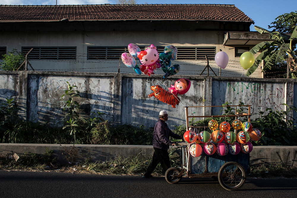 A balloon street vendor walks by the side of the road at sunset. August 18, 2018