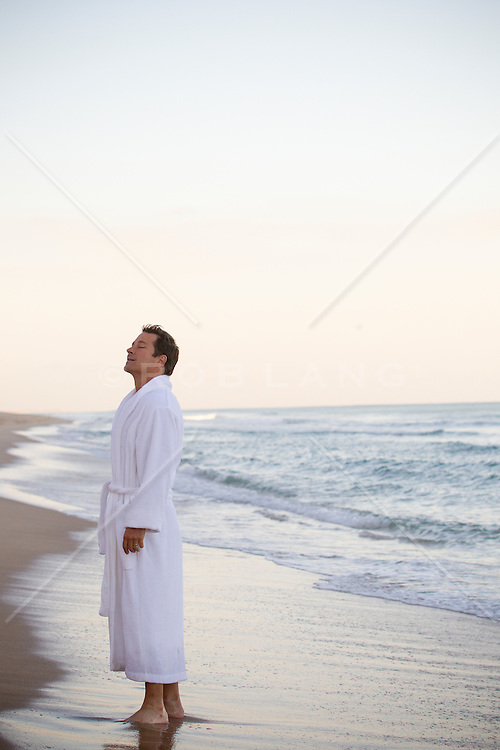 man standing in a white robe with his eyes closed enjoying the feel of the air and the ocean on a deserted beach in Florida