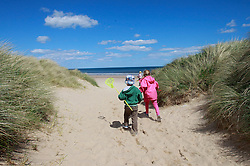 © Paul Thompson licensed to London News Pictures. 03/06/2015. Frances Tidswell-Thompson (7) and Nicholas Tidswell-Thompson (4) heading for Warkworth Beach Northumberland. Photo credit : Paul Thompson/LNP