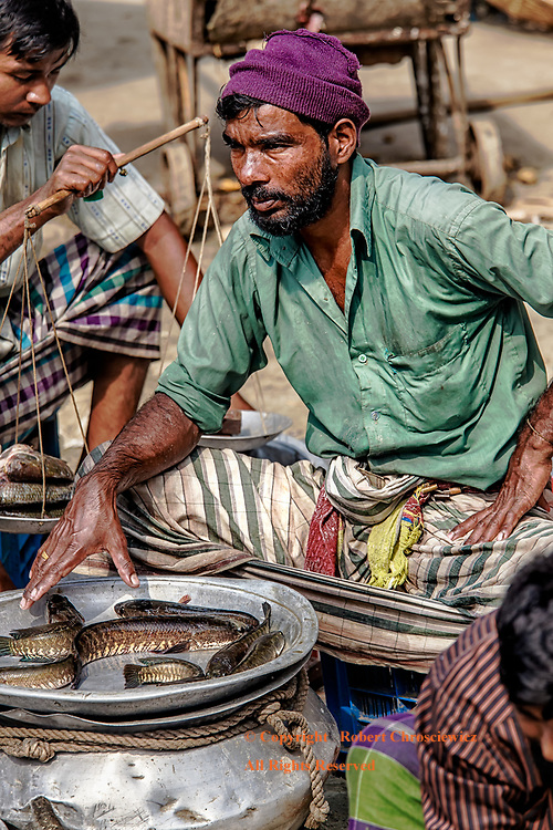 Dhaka Market:  Men sit patiently to sell their fish in a local market in Dhaka Bangladesh.