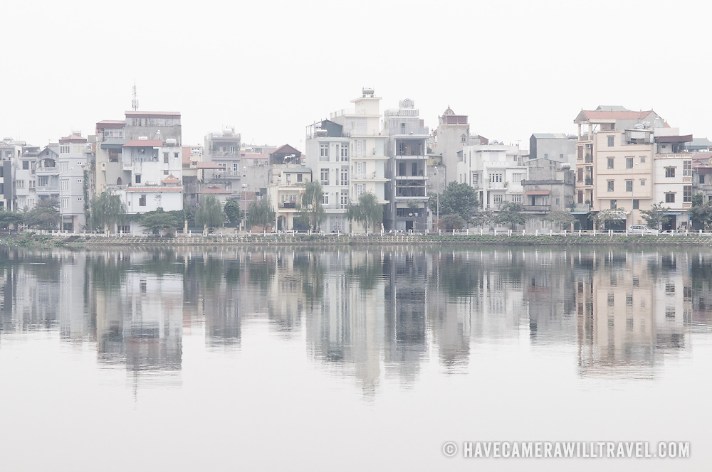 Buildings on the shore are reflected on the mirror-like surface of West Lake (Ho Tay) in Hanoi, Vietnam, on a hazy day.